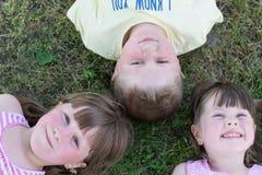 Trois enfants en bas âge se trouvant sur l'herbe Image stock