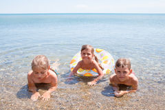 Trois enfants en mer Image stock