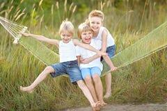 Trois enfants exécutent sur un fond coloré Photographie stock