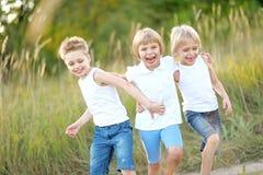 Trois enfants exécutent sur un fond coloré Photos stock
