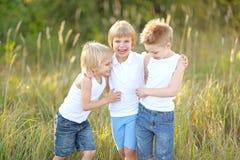 Trois enfants exécutent sur un fond coloré Images libres de droits