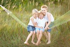 Trois enfants exécutent sur un fond coloré Photo stock