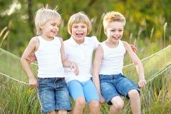 Trois enfants exécutent sur un fond coloré Photo libre de droits
