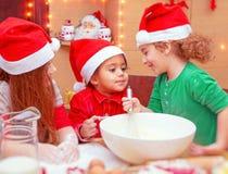 Trois enfants faisant des biscuits de Noël Photographie stock