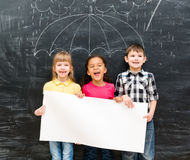 Trois enfants gais tenant la feuille de papier vide blanche Photo libre de droits