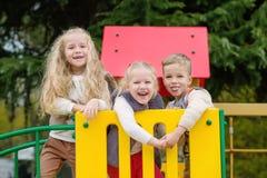 Trois enfants heureux ayant l'amusement ensemble Image libre de droits