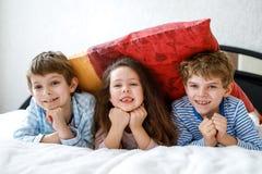 Trois enfants heureux dans des pyjamas célébrant la partie de pyjama École maternelle et écoliers et fille ayant l'amusement ense Image stock