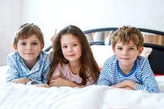 Trois enfants heureux dans des pyjamas célébrant la partie de pyjama École maternelle et écoliers et fille ayant l'amusement ense Images stock