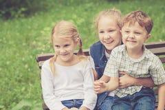 Trois enfants heureux jouant en parc au temps de jour Image libre de droits