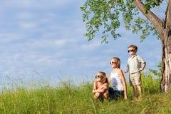 Trois enfants heureux jouant en parc au temps de jour Images libres de droits