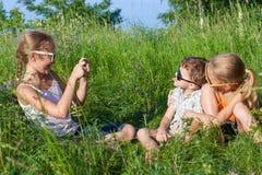 Trois enfants heureux jouant en parc au temps de jour Photo stock