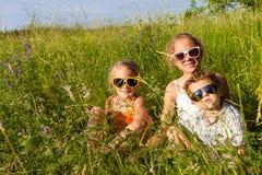 Trois enfants heureux jouant près de l'arbre au temps de jour Photographie stock libre de droits