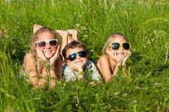 Trois enfants heureux jouant près de l'arbre au temps de jour Images libres de droits