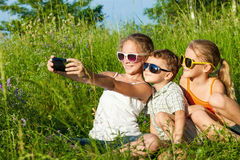 Trois enfants heureux jouant près de l'arbre au temps de jour Image stock