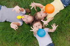 Trois enfants heureux jouant sur l'herbe au temps de jour Photographie stock libre de droits