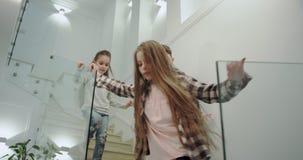 Trois enfants heureux le matin prêt pour l'école descendant aux escaliers dans une conception moderne de maison banque de vidéos