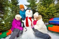 Trois enfants heureux s'asseyant près du bonhomme de neige mignon Photographie stock