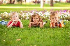Trois enfants heureux se trouvant sur la pelouse. Photos libres de droits