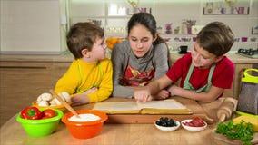 Trois enfants lisant le cuisinier réservent, faisant le dîner clips vidéos