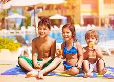 Trois enfants mangeant près de la piscine Photographie stock