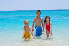Trois enfants marchant dans l'eau dans l'océan Images libres de droits