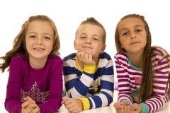 Trois enfants mignons fixant avec l'expression d'amusement Image stock