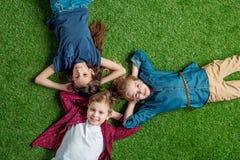 Trois enfants mignons se trouvant sur l'herbe avec des mains derrière des têtes et le sourire Photos stock