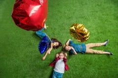 Trois enfants mignons se trouvant sur l'herbe verte avec des ballons Photo libre de droits