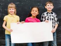 Trois enfants mignons tenant une feuille de papier vide pour l'annonce Photo libre de droits