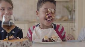Trois enfants ont un amusement se reposant ensemble à la table Il y a le gâteau enduit sur le visage de garçon Deux filles cau banque de vidéos