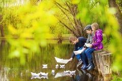 Trois enfants près de l'étang mettant les bateaux de papier Photographie stock libre de droits