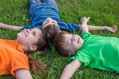 Trois enfants rêvants se couchant sur l'herbe verte Image libre de droits