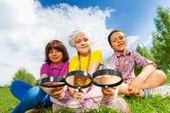 Trois enfants reposant la fin ainsi que des loupes Photo stock