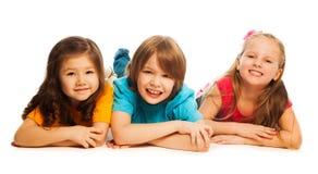 Trois enfants s'étendant dans la ligne Photo stock