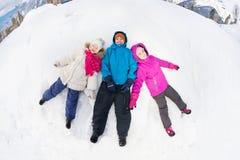 Trois enfants s'étendent sur la neige avec des jambes à part Images stock