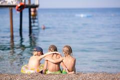 Trois enfants s'asseyant sur une plage Photo stock