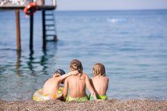 Trois enfants s'asseyant sur une plage Photos stock