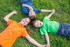 Trois enfants se couchant sur l'herbe verte Photo stock