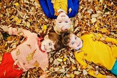 Trois enfants se situant dans des feuilles tombées Photos stock