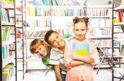 Trois enfants se tenant dans une rangée avec des livres Photos stock