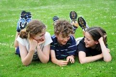 Trois enfants se trouvant sur l'herbe au stationnement Photographie stock