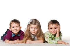 Trois enfants sur le tapis Image stock