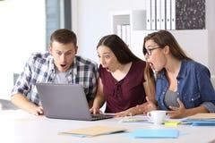 Trois entrepreneurs stupéfaits sur la ligne au bureau Images stock