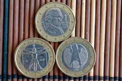 Trois euro pièces de monnaie se trouvent sur la table en bambou en bois dans une dénomination de rangée est deux l'euro - arrière Photos stock