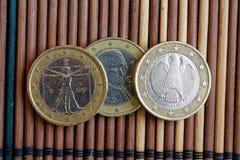 Trois euro pièces de monnaie se trouvent sur la table en bambou en bois dans une dénomination de rangée est 2 l'euro - arrière Photographie stock libre de droits