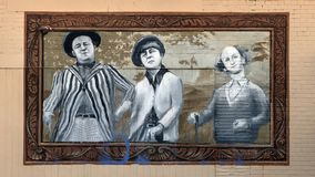 Trois faire-valoir jouant au golf la peinture murale, Dallas, le Texas Photo stock