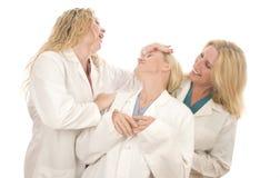 Trois femelles médicales d'infirmières avec l'expression heureuse Photos libres de droits