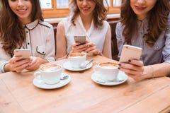 Trois femmes à l'aide des smartphones en café Photographie stock