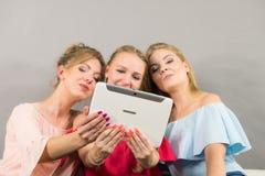 Trois femmes à l'aide du comprimé Photographie stock libre de droits