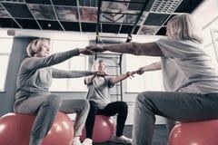 Trois femmes agées tenant des mains tout en se reposant sur des boules d'exercice Image libre de droits